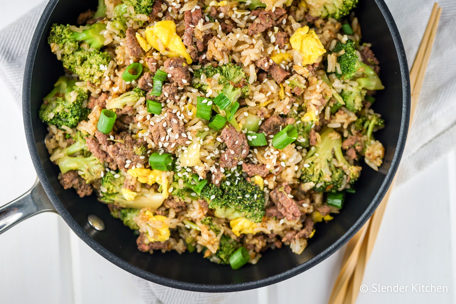 Beef and Broccoli Fried Rice in a pan with a wooden spoon.