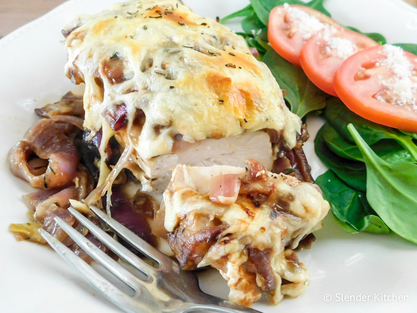 French Onion Soup Chicken on a plate with lettuce and tomato salad.