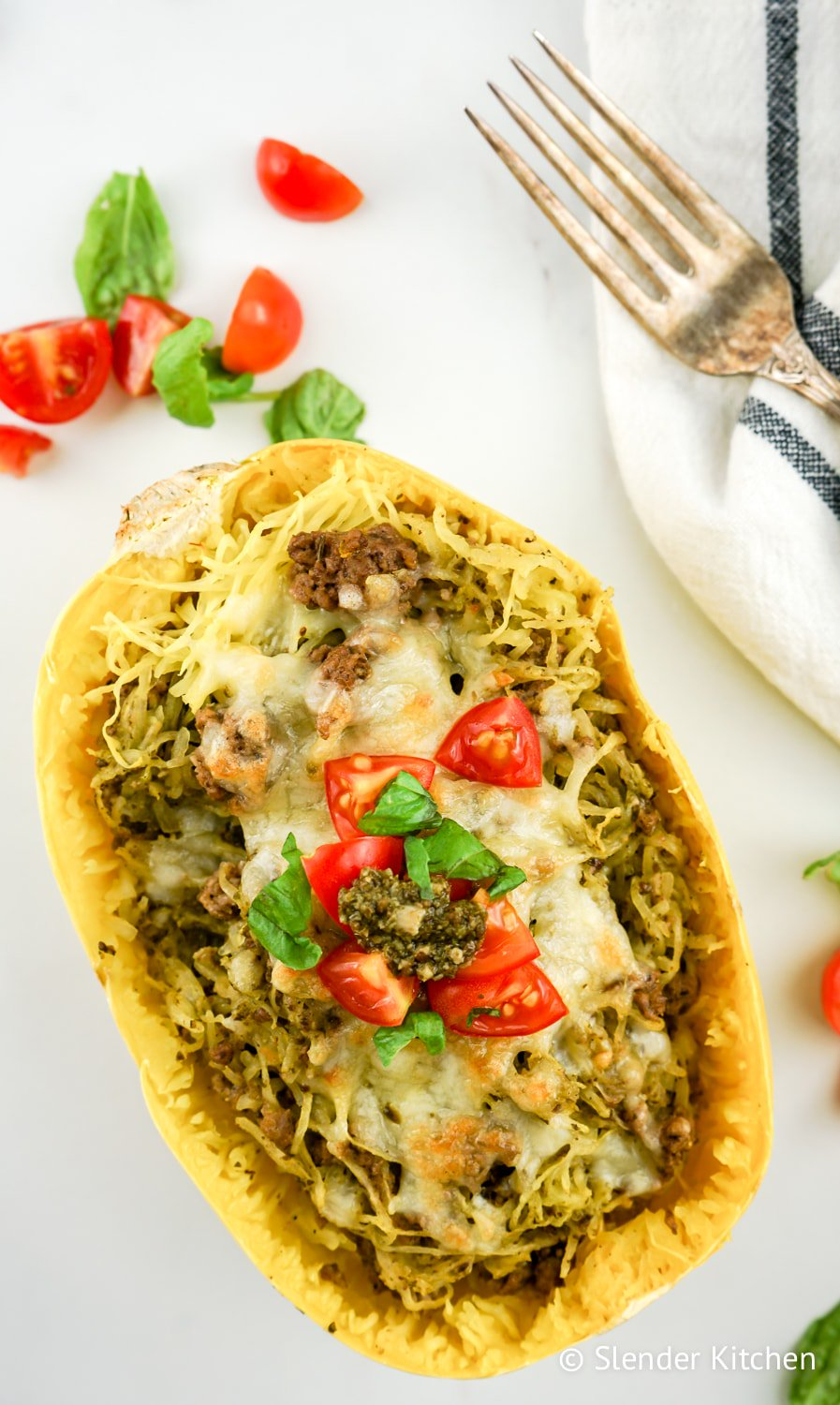 Weight Watchers Pesto Spaghetti Squash on a marble background with tomato slices.