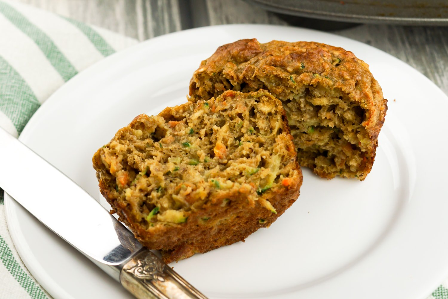 Healthy Zucchini Carrot Muffins in a muffin tin with a cup of tea.