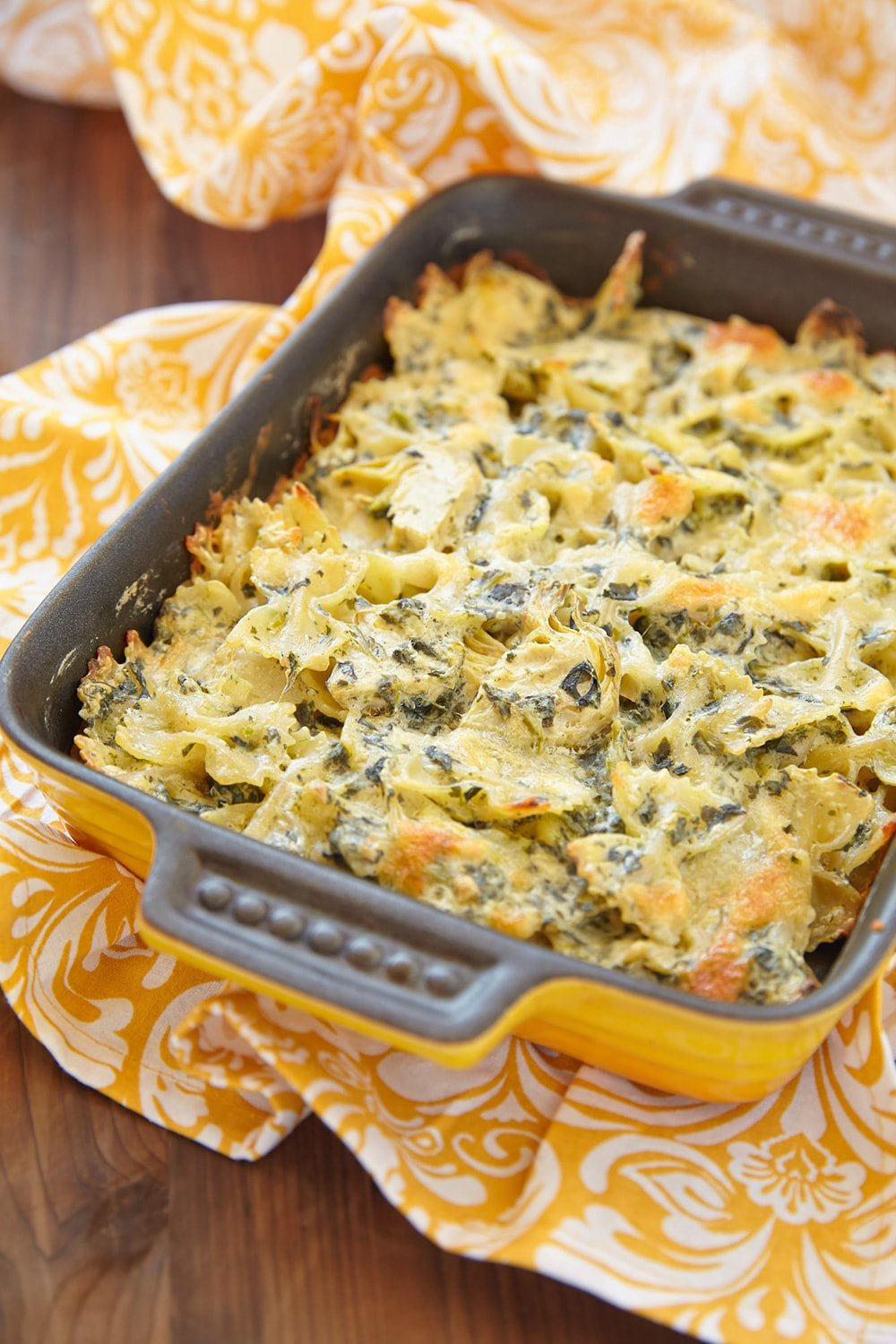 Healthy Spinach Artichoke Pasta in a baking dish with yellow napkin.