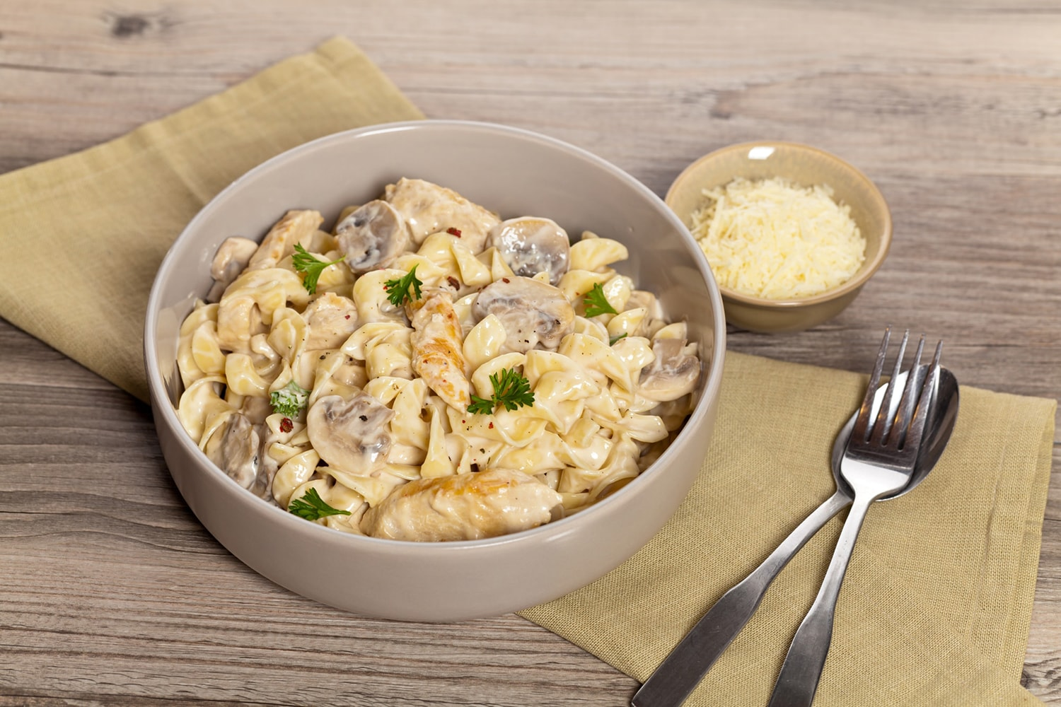 Healthy One Pot Chicken Mushroom Pasta in a dish with a wooden spoon.