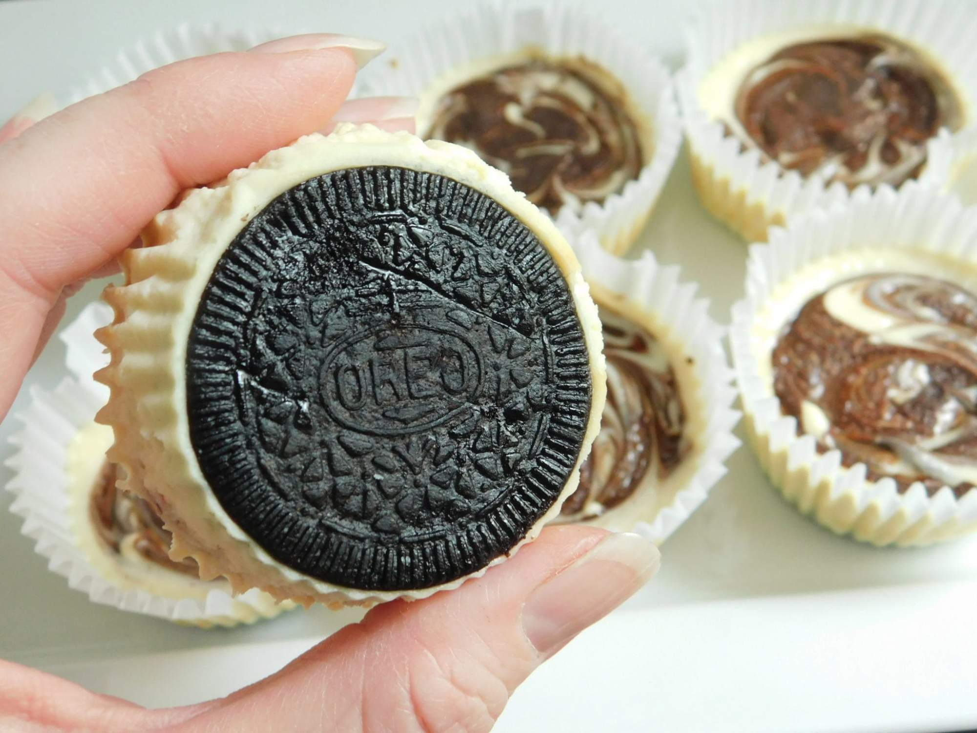 Skinny Oreo Cheesecakes with a chocolate swirl in a cupcake tin.