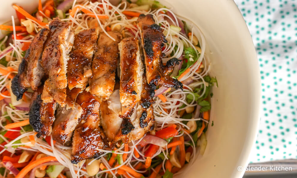 Asian Noodle Salad with Chicken in a beige bowl with noodles, veggies, and peanuts.