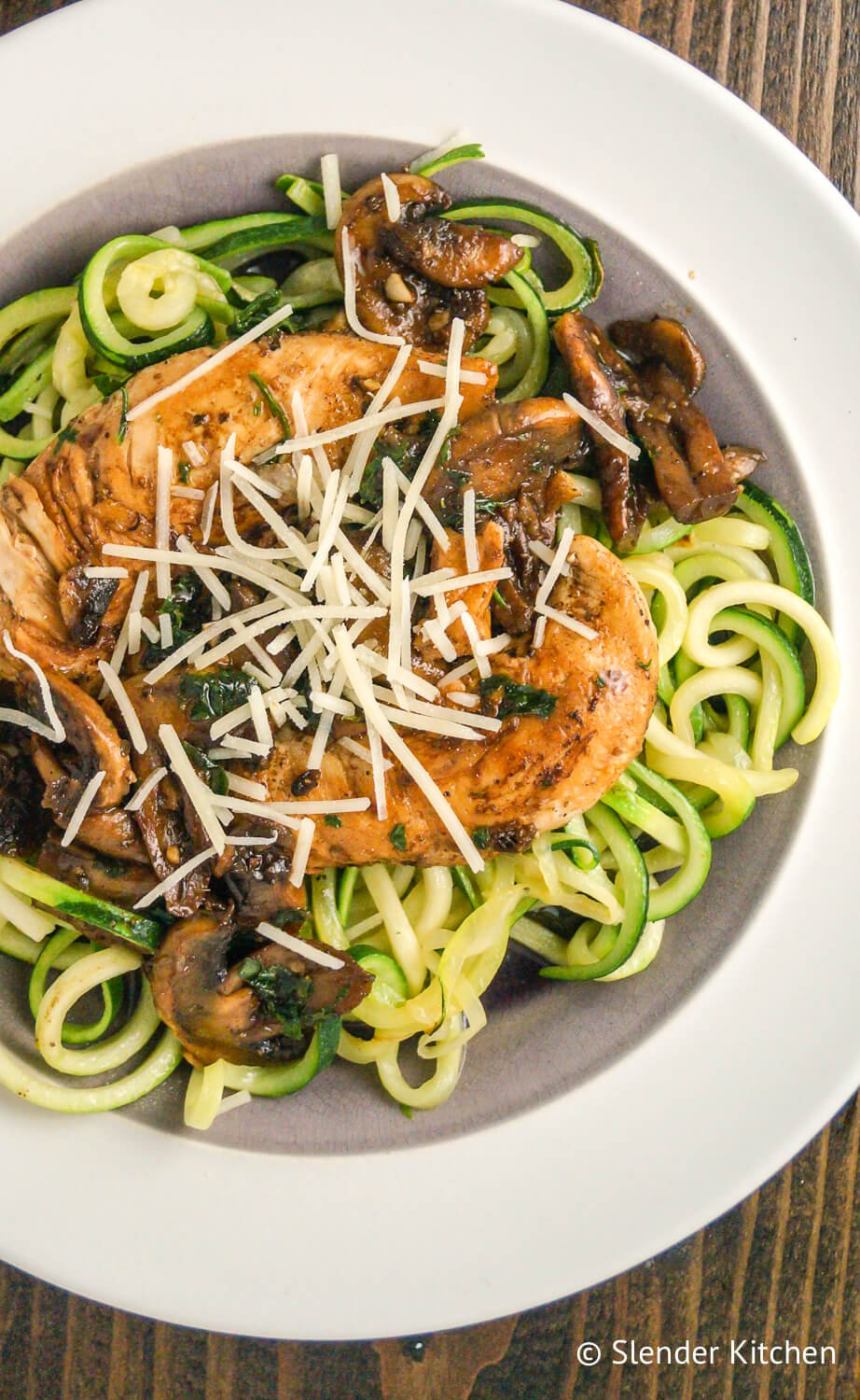 Balsamic chicken with zucchini noodles on a white plate and wood background.