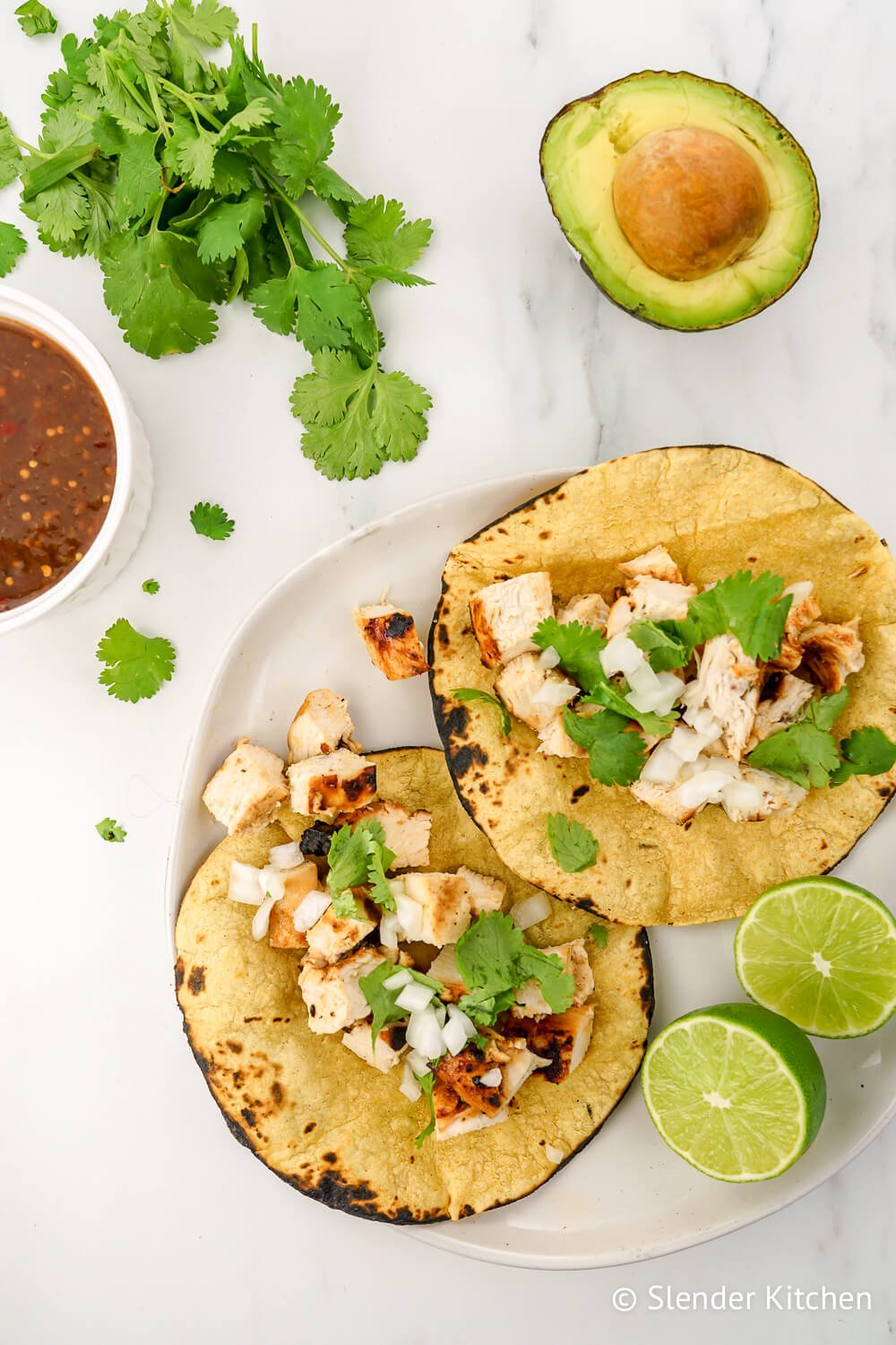 Chicken tacos with cilantro and avocado on a marble background.