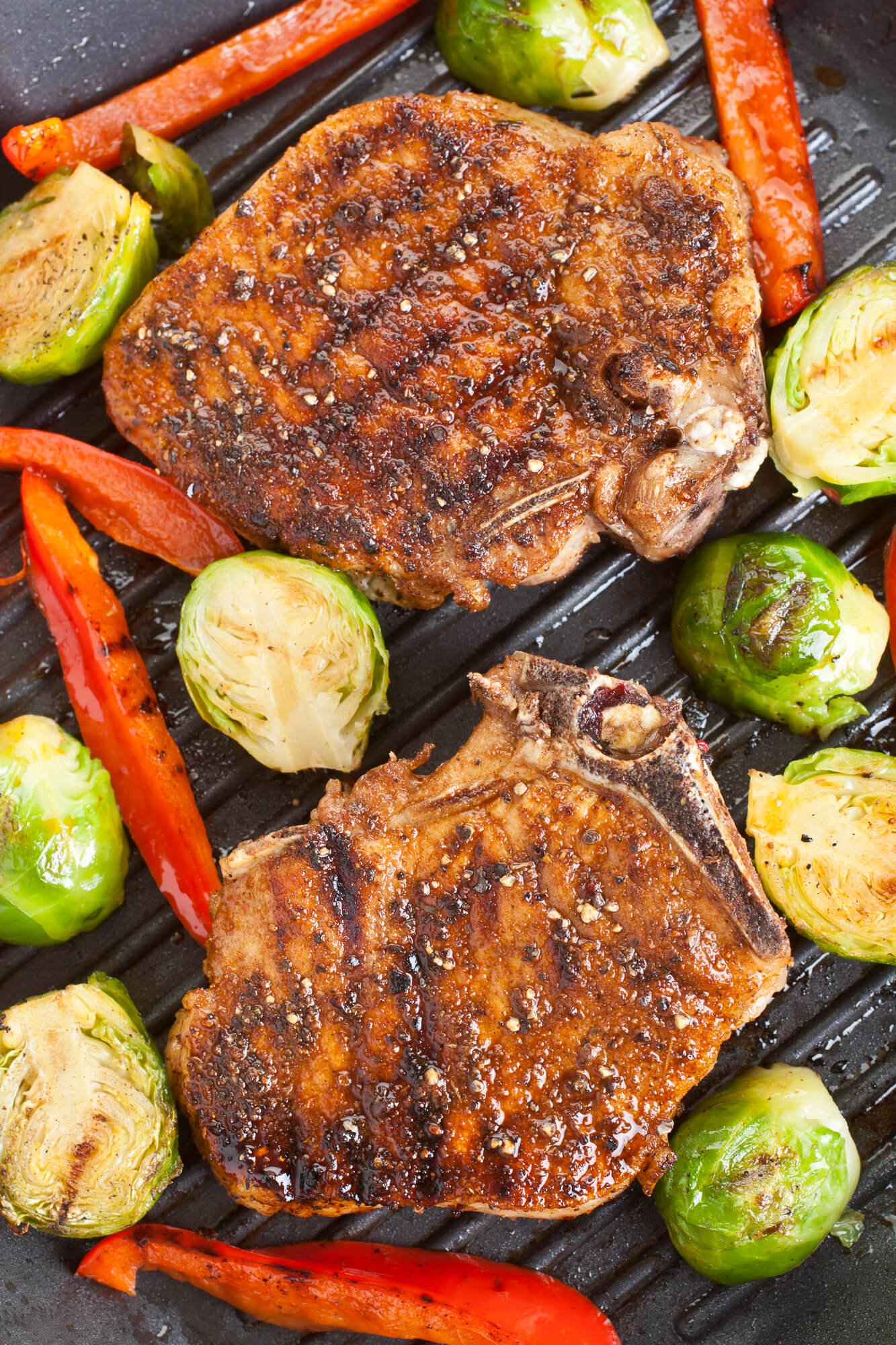 Grilled Pork Chops with peppers and Brusslels sprouts on a grill pan.