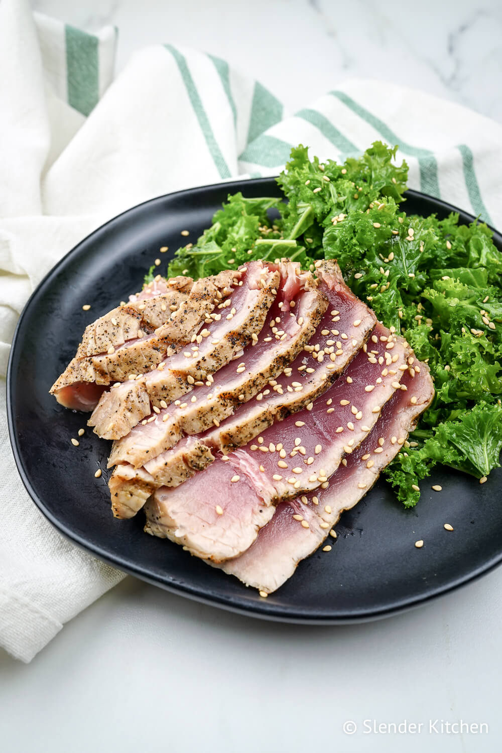 Grilled tuna steak on a black plate with kale salad and a green and white napkin.