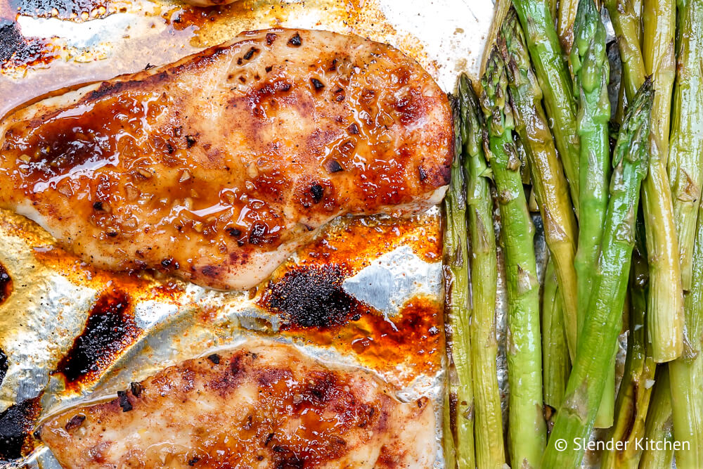 Chicken and asparagus in a honey mustard sauce on foil.