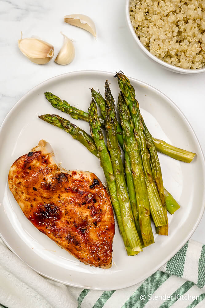 Chicken with asparagus and quinoa on a white plate with garlic on the side.