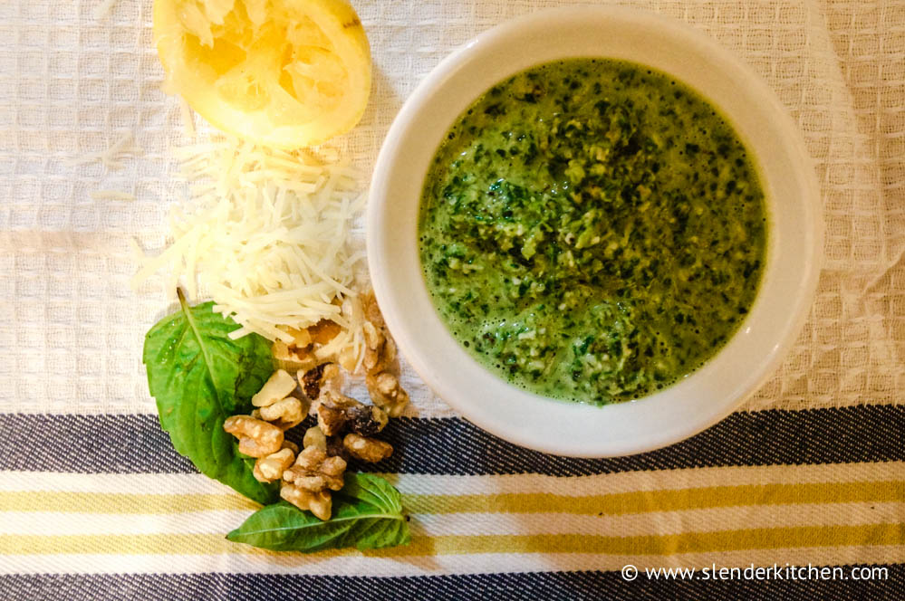 Skinny pesto sauce in a jar with lemon and basil on the side.