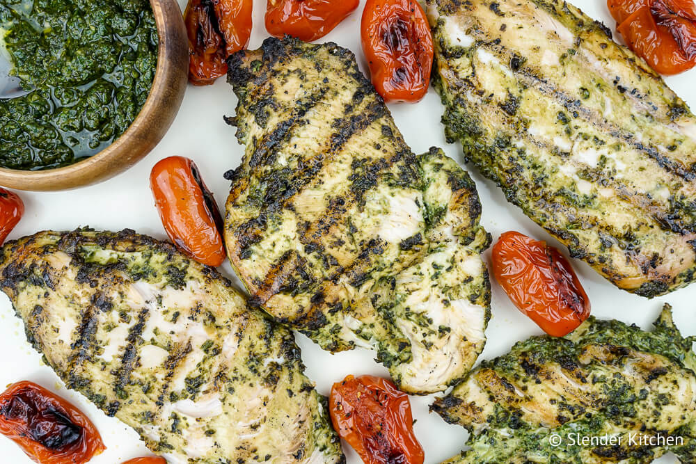 Skinny pesto sauce with chicken with tomatoes on a marble board.